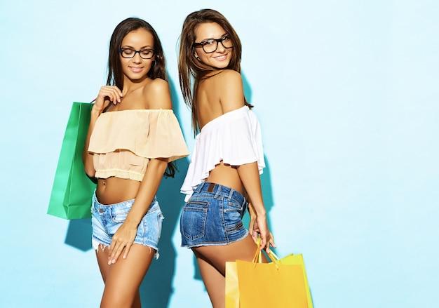 Porträt von zwei jungen stilvollen lächelnden brunettefrauen, die einkaufstaschen halten. frauen gekleidet in sommer hipster kleidung. positive modelle, die über blauer wand aufwerfen