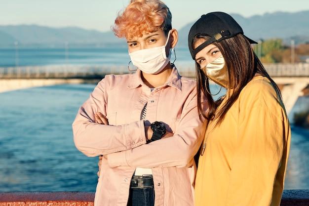 Porträt von zwei jungen tausendjährigen freunden, die eine gesichtsmaske tragen, um eine coronavirus-infektion zu verhindern, covid-19 - menschen, die gemeinsam spaß haben - konzept der freiheit.