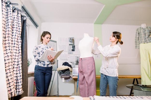 Porträt von zwei jungen weiblichen modedesignern oder schneidern, mannequin messend, klebeband haltend, mit dummy im gemütlichen kreativen designstudio oder schneiderei arbeitend, schneiderei und nähkonzept