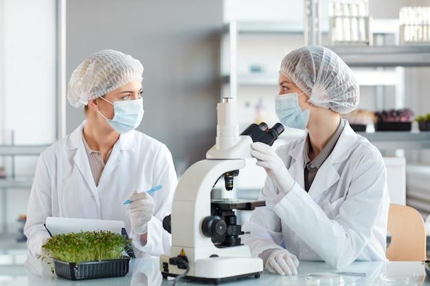 Porträt von zwei jungen wissenschaftlerinnen, die im mikroskop schauen, während sie pflanzenproben im biotechnologielabor studieren, raum kopieren
