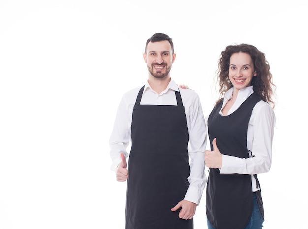 Porträt von zwei kellnern auf dem weißen hintergrund. paar arbeitet im café