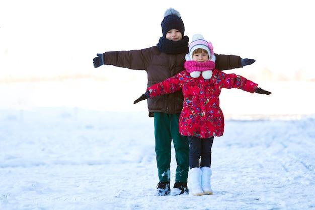 Porträt von zwei kindern, die draußen im verschneiten wintertag spielen