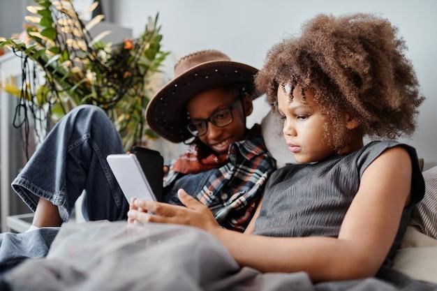 Porträt von zwei kindern im teenageralter, die zusammen smartphone benutzen, während sie zu hause auf dem bett liegen