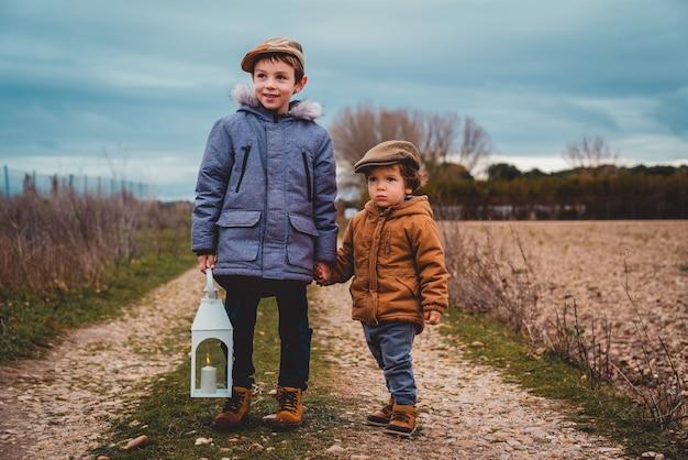 Porträt von zwei kindern mit einer laterne im herbst händchen haltend auf einer landstraße an einem bewölkten tag