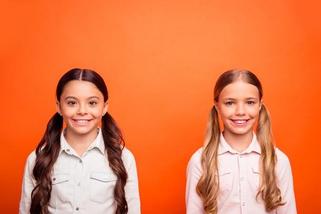 Porträt von zwei kleinen kindern, die zusammen stehen und spaß am wochenendlächeln haben, fühlen sich offen, tragen lässige stilkleidung, die über orangefarbenem hintergrund isoliert wird