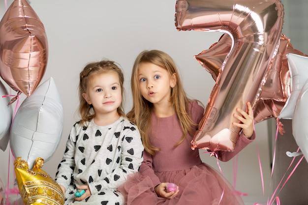 Porträt von zwei kleinen netten mädchen, die auf dem boden mit ballonen sitzen
