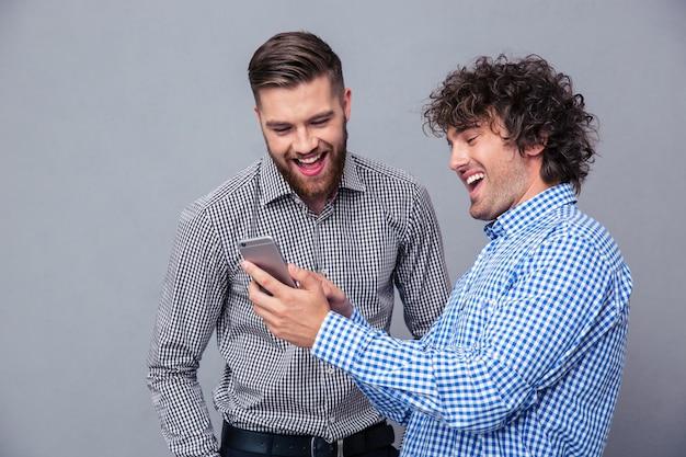 Porträt von zwei lachenden männern, die smartphone über graue wand verwenden