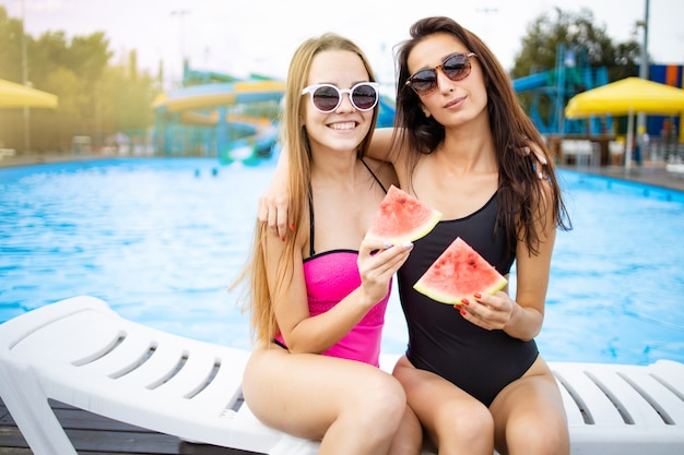 Porträt von zwei lächelnden freundinnen mit einer scheibe wassermelone. viel spaß am pool mit freunden gesellschaft. sommer strandparty.
