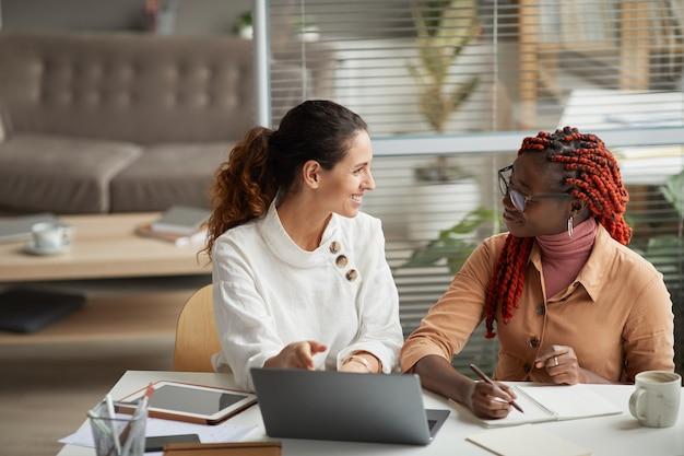 Porträt von zwei lächelnden geschäftsfrauen, die projekt besprechen, während sie zusammen am schreibtisch sitzen und am start im büro arbeiten, raum kopieren