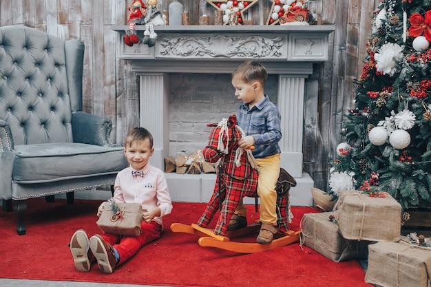 Porträt von zwei lächelnden kindern, die geschenkbox in der weihnachtszeit halten