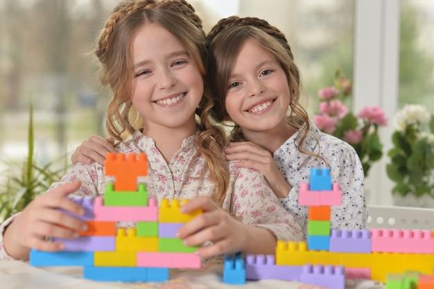 Porträt von zwei lächelnden kleinen mädchen, die spielwaren spielen