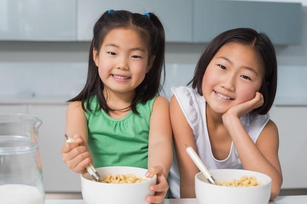 Porträt von zwei lächelnden mädchen, die mit schüsseln in der küche sitzen