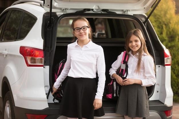 Porträt von zwei lächelnden mädchen, die schultaschen aus dem kofferraum nehmen