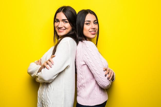 Porträt von zwei lächelnden mädchen gekleidet in pullovern, die rücken an rücken lokalisiert über gelber wand stehen