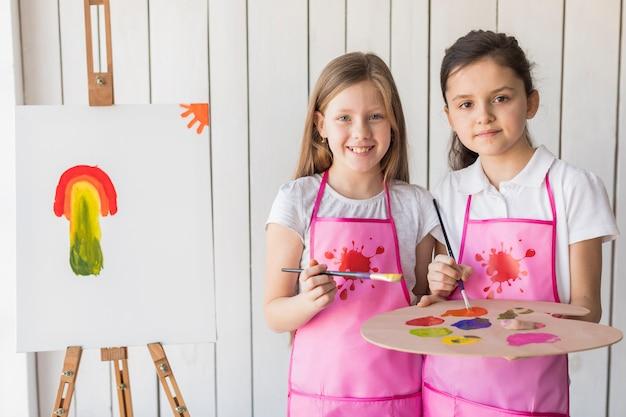 Porträt von zwei lächelnden mädchen im rosa schutzblech, das kamera beim malen auf dem gestell betrachtet