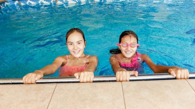 Porträt von zwei lächelnden mädchen im teenageralter beim schwimmen im pool