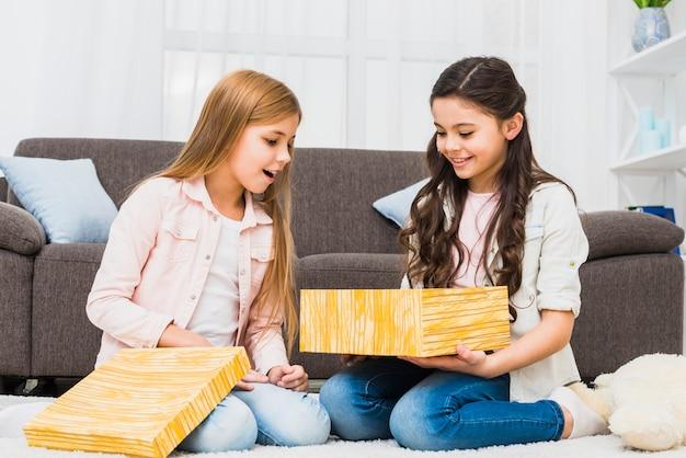 Porträt von zwei lächelnden mädchen, welche die geschenkbox sitzt im wohnzimmer betrachten