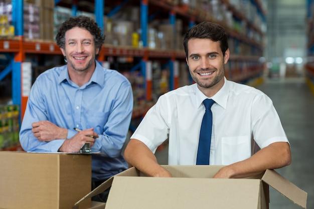Porträt von zwei lagerarbeitern, die zusammen mit kisten stehen
