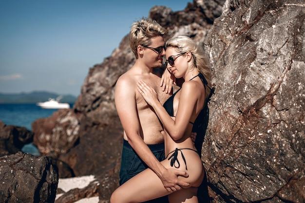 Porträt von zwei liebenden jungen und mädchen in badeanzügen, die zusammen posieren, sich umarmen und gegen die felsen und steine lächeln.