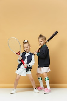 Porträt von zwei mädchen als tennisspieler, die tennisschläger halten.