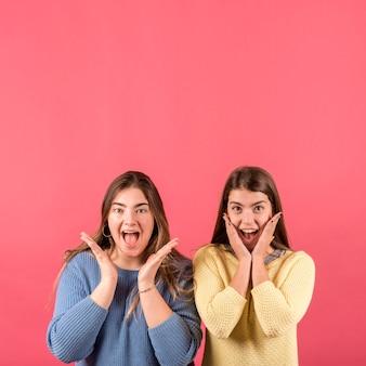 Porträt von zwei mädchen auf rotem hintergrund