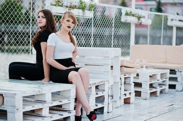 Porträt von zwei mädchen, die auf bank am pier sitzen