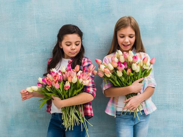Porträt von zwei mädchen, die vor der blauen wand hält tulpenblumenblumenstrauß stehen