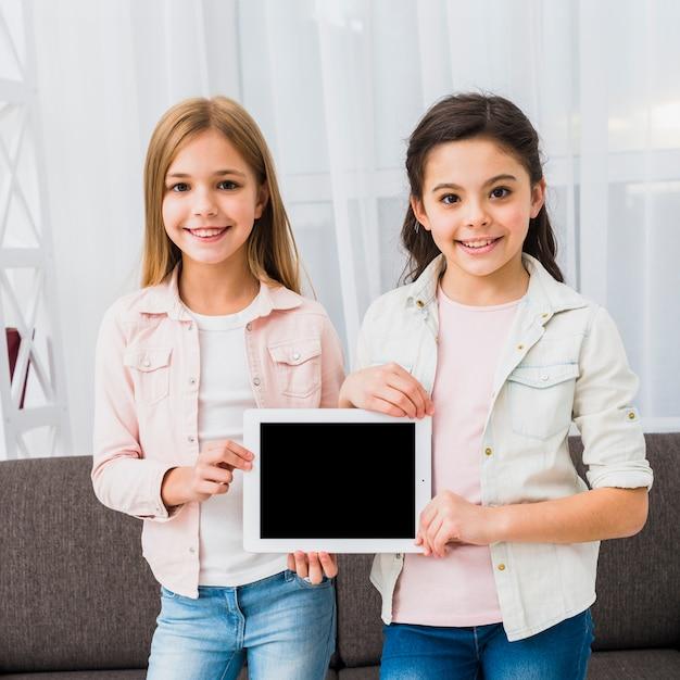 Porträt von zwei mädchen, die zu hause digitale tablette des leeren bildschirms zeigen