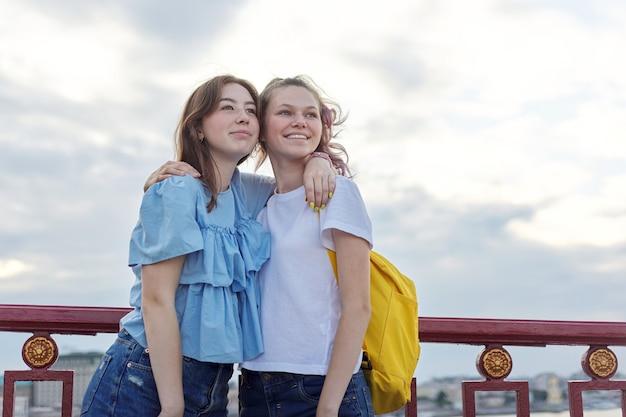 Porträt von zwei mädchen im teenageralter, die auf der brücke über den fluss stehen, freunde gehen am sonnigen sommertag. freundschaft, lifestyle, jugend, teenager