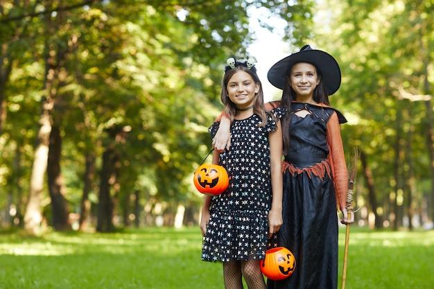 Porträt von zwei mädchen in hexenkostümen, die an der kamera lächeln, während im park draußen stehen