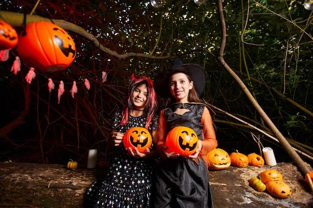 Porträt von zwei mädchen in kostümen, die spielzeugkürbisse halten und in die kamera lächeln, sind sie auf der party im dunkeln