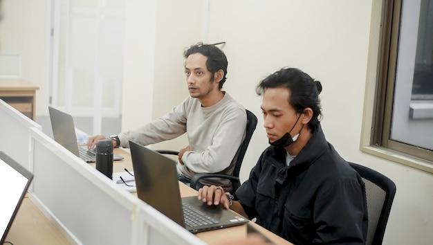 Porträt von zwei männern, die in einem meeting mit ihrem chef im fokus stehen