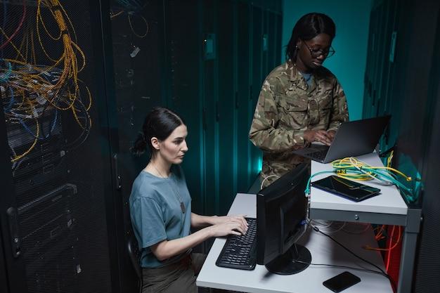 Porträt von zwei militärischen jungen frauen, die computer verwenden, während sie im serverraum zusammenarbeiten und ein netzwerk einrichten, raum kopieren