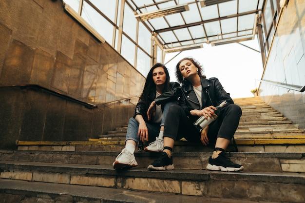 Porträt von zwei modellen in stilvoller freizeitkleidung, die auf treppe mit flasche wein in der hand sitzen