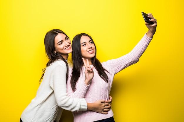 Porträt von zwei reizenden mädchen gekleidet in pullovern, die stehen und ein selfie nehmen, das über gelber wand isoliert wird