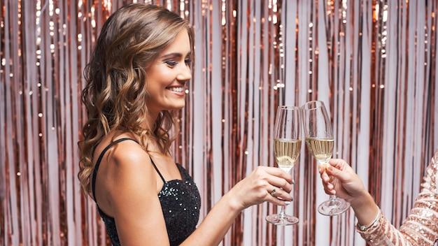 Porträt von zwei schönen eleganten frauen, die champagnergläser klirren.