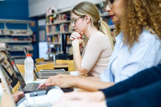 Porträt von zwei schönen jungen frauen, die in einer universitätsbibliothek studieren.