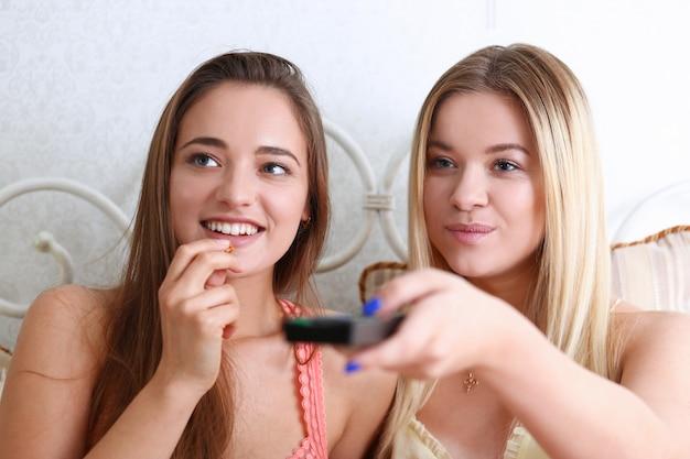 Porträt von zwei schönen jungen lächelnden freundinnen, die ein komödienfilmmelodramma in einer wohnung isst popcorn und lacht aufpassen