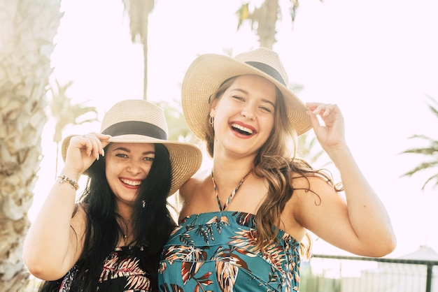 Porträt von zwei schönen und fröhlichen freundinnen, die während der sommerferien strohhüte im freien halten. fröhliche modische weibliche touristen mit strohhüten
