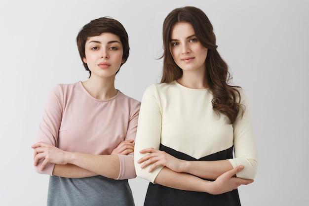 Porträt von zwei schönen universitätsfreundinnen mit dunklem haar, die für abschlussfotoalbum in modischen kleidern aufwerfen.