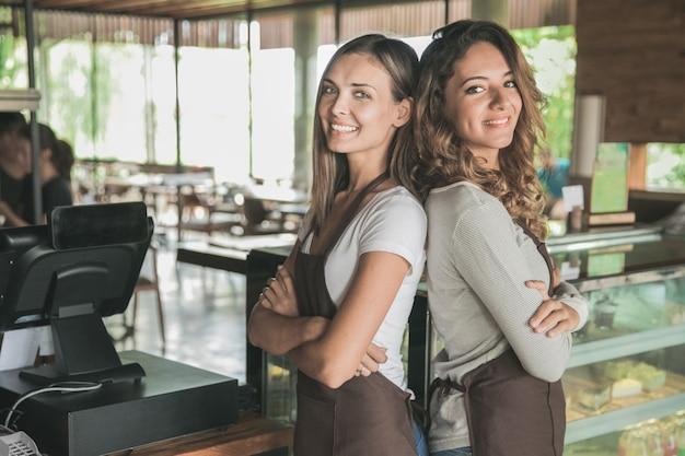 Porträt von zwei schönen weiblichen kellnerin, die zur kamera lächelt