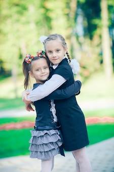 Porträt von zwei schwestern, die auf der straße stehen, die sich umarmen und mit lächeln und glücklichen gesichtern in die kamera schauen