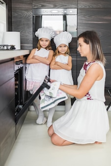 Porträt von zwei schwestern, die in küche aufwerfen, während mutter plätzchen in ofen einsetzt