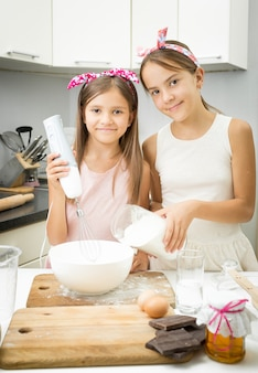 Porträt von zwei schwestern, die zutaten für teig in einer großen schüssel in der küche mischen