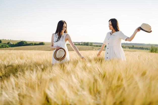 Porträt von zwei schwestern in weißen kleidern mit langen haaren auf einem feld
