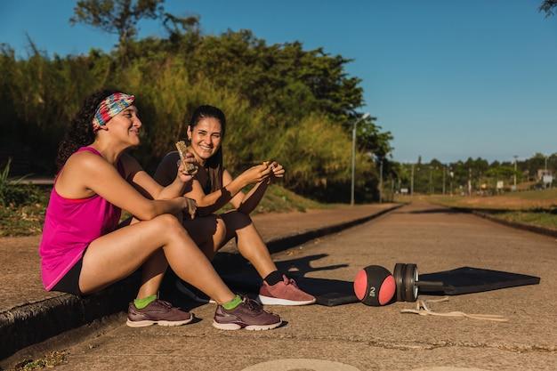 Porträt von zwei sportlerinnen, die auf der straße ruhen und einen müsliriegel essen