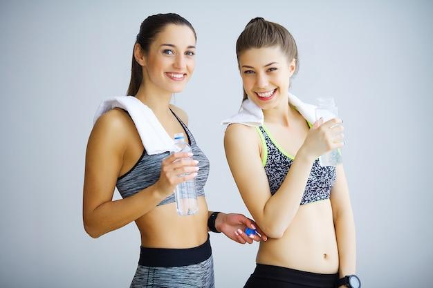 Porträt von zwei sportlichen jungen damen mit den wasserflaschen und tuch, die in der turnhalle aufwerfen.