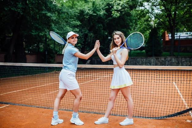 Porträt von zwei sportlichen mädchen auf gericht, tennisspieler mit schlägern beendete wettbewerb.