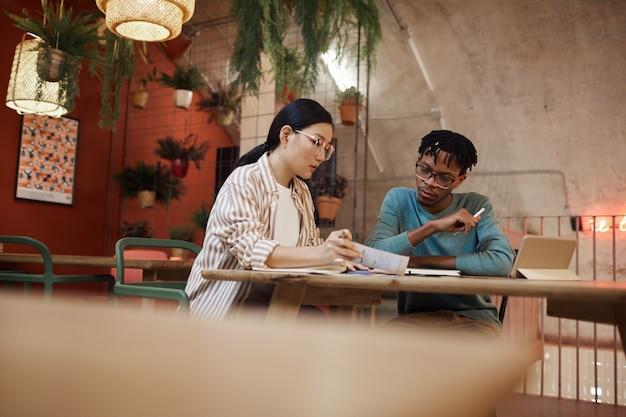 Porträt von zwei studenten, die zusammen am projekt arbeiten, während sie am tisch im café studieren