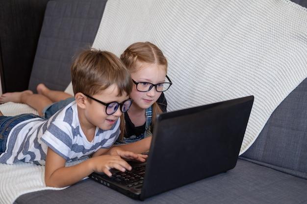 Porträt von zwei süßen kaukasischen kindern in brillen mit laptop beim lernen zu hause, fernbildungskonzept. auf der couch liegen. geschwister. quarantäne. zurück zum schulkonzept.